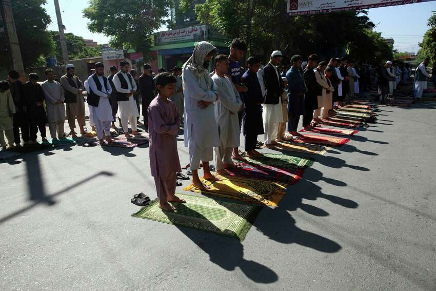 Men attend the Eid al-Fitr prayers outside a mosque in Kabul, Afghanistan, Sunday, May 24, 2020. The Taliban and Afghanistan's president announced late Saturday a three-day cease-fire ahead of a major Islamic holiday that begins Sunday to mark the end of the Islamic fasting month of Ramadan.