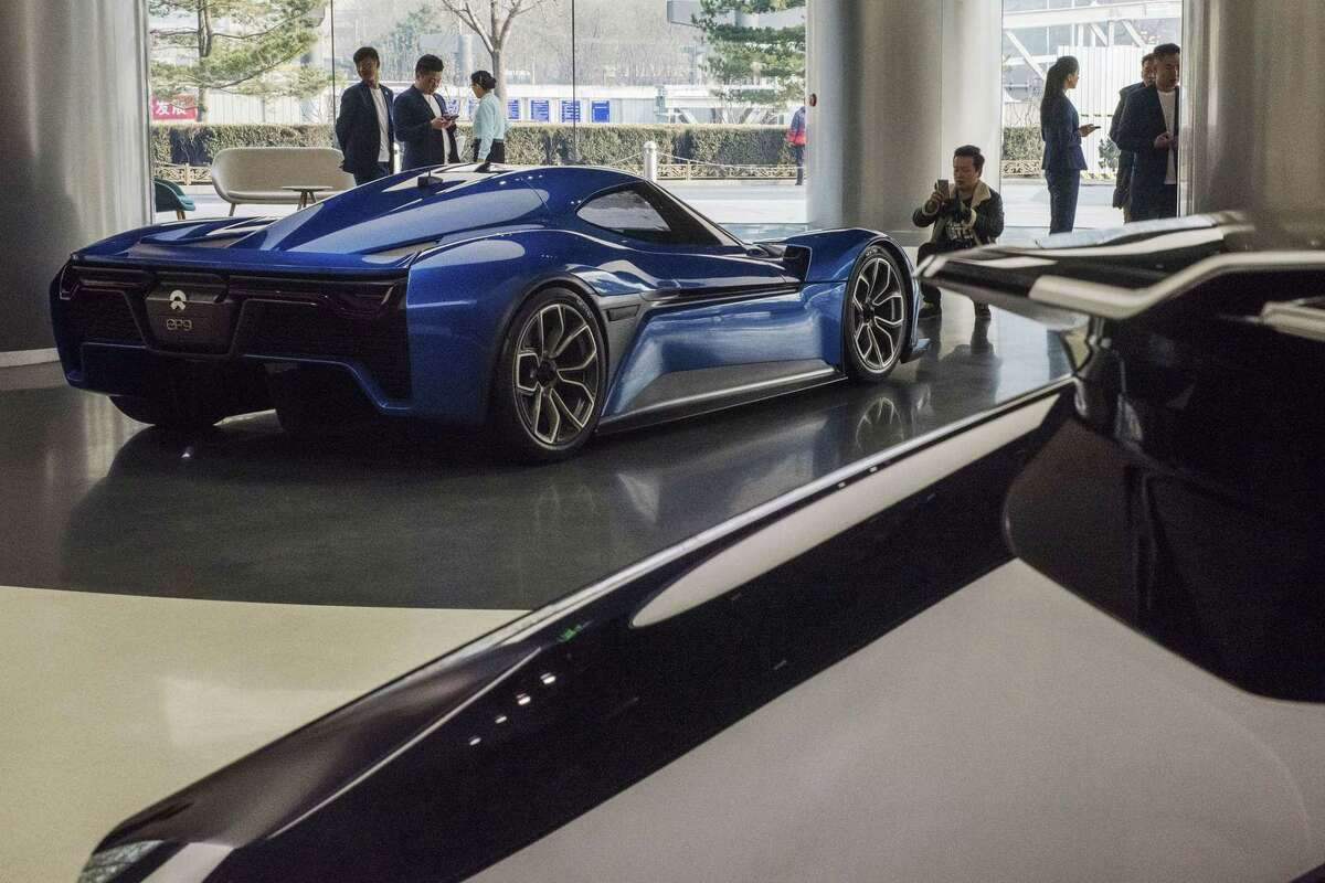 A visitor takes a photograph of a NIO EP9 autonomous electric vehicle (EV) on display at the company's NIO House brand experience center in Beijing on Dec. 2, 2017.