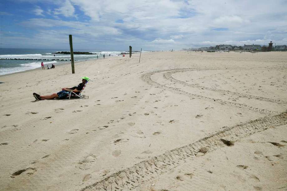 Kevin Heine relaxes on a mostly empty beach Saturday, May 23, 2020, in Belmar, N.J., during the coronavirus pandemic. Photo: John Minchillo, AP / Copyright 2020 The Associated Press. All rights reserved.