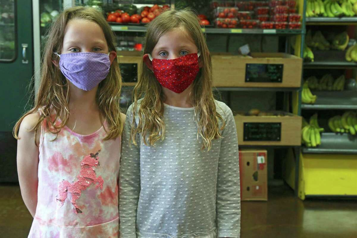 Mia Mason, 6, left, of Fairfield, and her twin sister Emma do some shopping at The Pantry on Friday, May 22, 2020, in Fairfield, Conn.