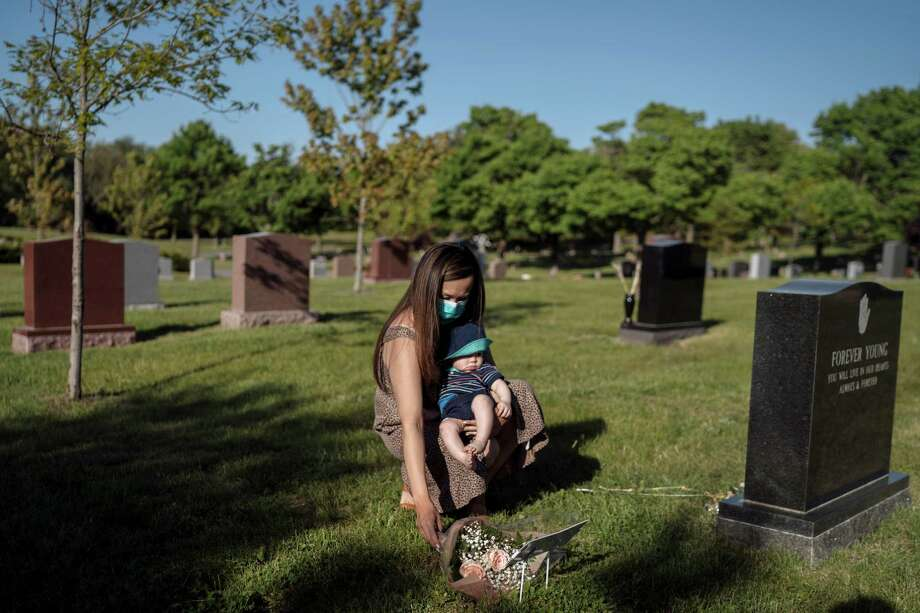 Elaine Eklund holds her son as they visit the grave of Elaine's mother, Yok Yen Lee, who died from covid-19. Lee was among 34 Walmart employees in Quincy, Mass., who tested positive for the coronavirus. Photo: Photo For The Washington Post By Hannah Reyes Morales / Hannah Reyes Morales for The Washington Post