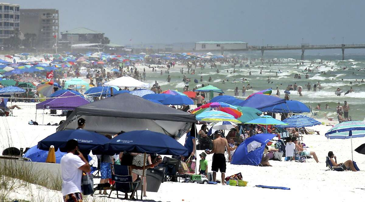 People pack the beaches on Okaloosa Island, Fla., Saturday, May 23, 2020, as the long Memorial Day weekend begins. Vacationers from Texas, Georgia, Alabama, and Arkansas have crowded the reopened beaches after the lifting of many state's stay-at-home restrictions due to the coronavirus pandemic. (Michael Snyder/Northwest Florida Daily News via AP)