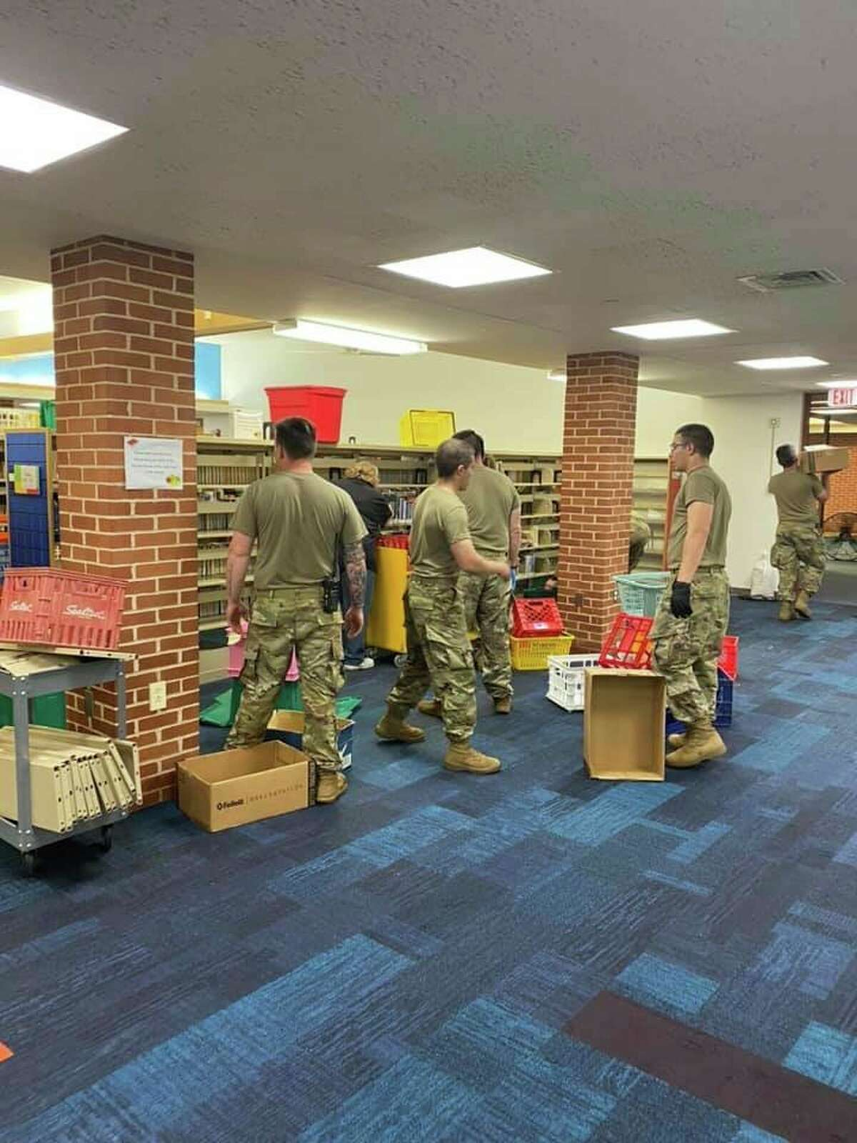 Members of the Michigan National Guard help transfer books from Grace A. Dow Memorial Library's flooded lower level on Thursday, May 21. (Photo provided/Facebook)