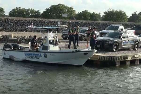 A boat with the Montgomery County Precinct 1 Constable's Office is seen on parked at a pier on Lake Conroe as authorities on Saturday search for a man who drowned.