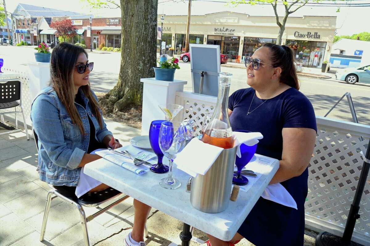 Nicole Kapoutsos, left, and Kelly Linskey, both of Fairfield, have an outdoor lunch on Friday, May 22, 2020, in Fairfield, Conn.