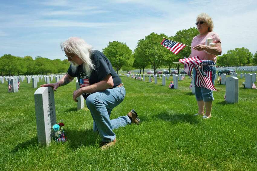 Navy veteran Donald Amorosi, left, and his wife Sharon Amorosi of South Glens Falls place a flag and flowers at the grave of Army veteran Chad Byrne at the Gerald B.H. Solomon Saratoga National Cemetery on Sunday, May 24, 2020, in Schuylerville, N.Y. The Amorosis visit 15 graves of friends and the children of friends. The couple has been doing this for over 14 years. Donald Amorosi served during Vietnam. Amorosi met Byrne in 2008, just before his death. (Paul Buckowski/Times Union)