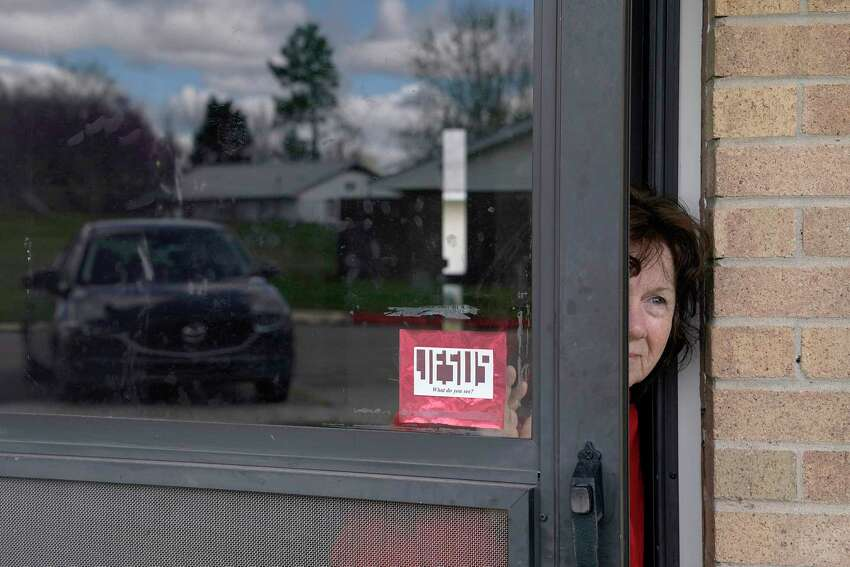 Patricia Flood, who has COPD and other health issues, peeks out of her front door in Bristow, Okla.