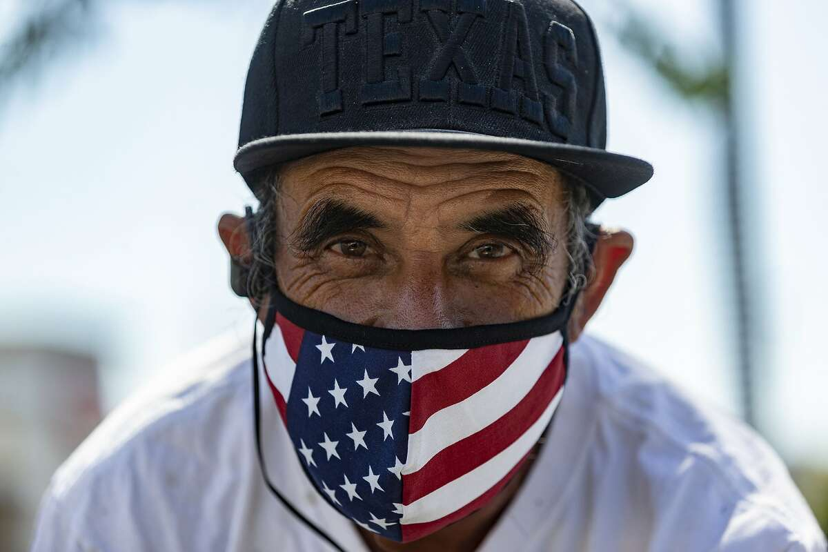 Street seller Jaime Caldera, originally from San Antonio, Texas, offers face masks for sale in Los Angeles Thursday, May 14, 2020. Leaving home in Los Angeles now requires bringing a face covering, part of the price for reopening more businesses and activities in America's second-largest city, which is moving cautiously as less-populated areas of California press ahead. The mask rule is the same in surrounding Los Angeles County, which has emerged as California's epicenter for the virus. The county has a quarter of California's nearly 40 million people but more than half of its more than 3,000 virus deaths. (AP Photo/Damian Dovarganes)