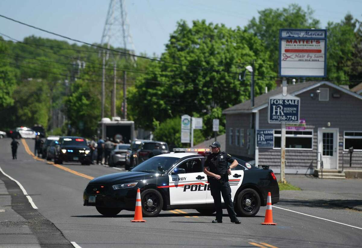Traffic is diverted as local and state police respond to a homicide on Roosevelt Drive in Derby, Conn. Sunday, May 24, 2020. A male victim was found dead at the home Sunday morning. Authorities have been searching for a suspect, 23-year-old Peter Manfredonia, who they say is connected to a Friday homicide in Willington as well as Sunday's homicde in Derby.