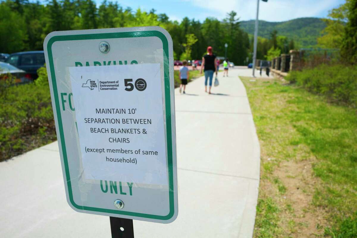 Signs are posted at Million Dollar Beach on Sunday, May 24, 2020, in Lake George, N.Y. New rules are in effect to help stop the spread of coronavirus. People must wear masks when moving around the beach but masks can be removed when swimming or when sitting on the sand. (Paul Buckowski/Times Union)