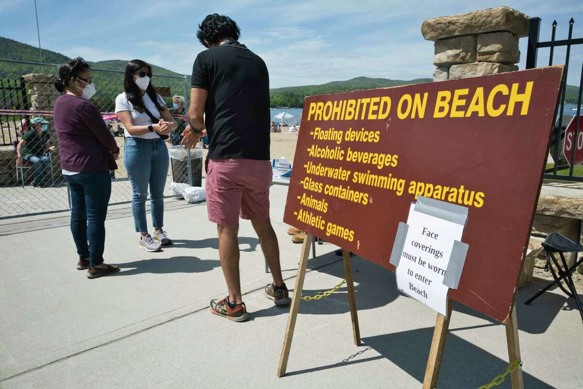 People disinfect their hands before going into Million Dollar Beach on Sunday, May 24, 2020, in Lake George, N.Y. New rules are in effect to help stop the spread of coronavirus. People must wear masks when moving around the beach but masks can be removed when swimming or when sitting on the sand. (Paul Buckowski/Times Union)