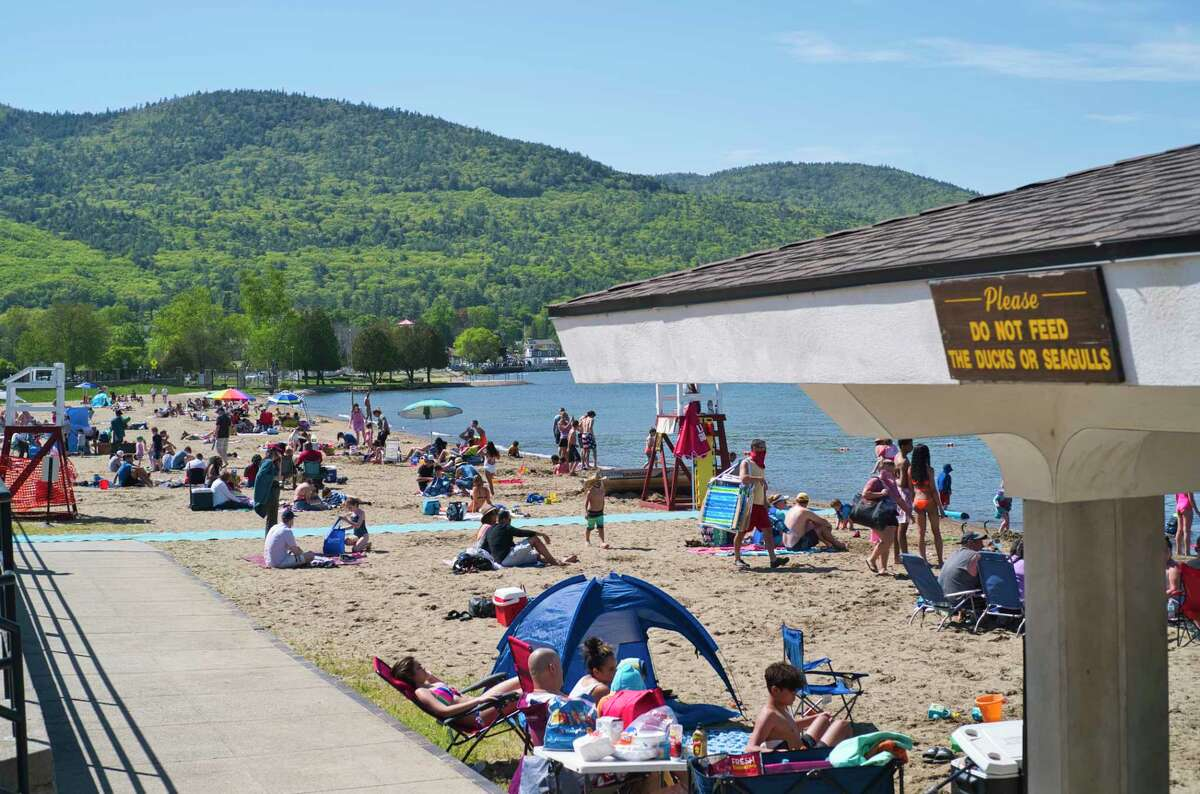 People enjoy an afternoon at Million Dollar Beach on Sunday, May 24, 2020, in Lake George, N.Y. New rules are in effect to help stop the spread of coronavirus. People must wear masks when moving around the beach but masks can be removed when swimming or when sitting on the sand. (Paul Buckowski/Times Union)