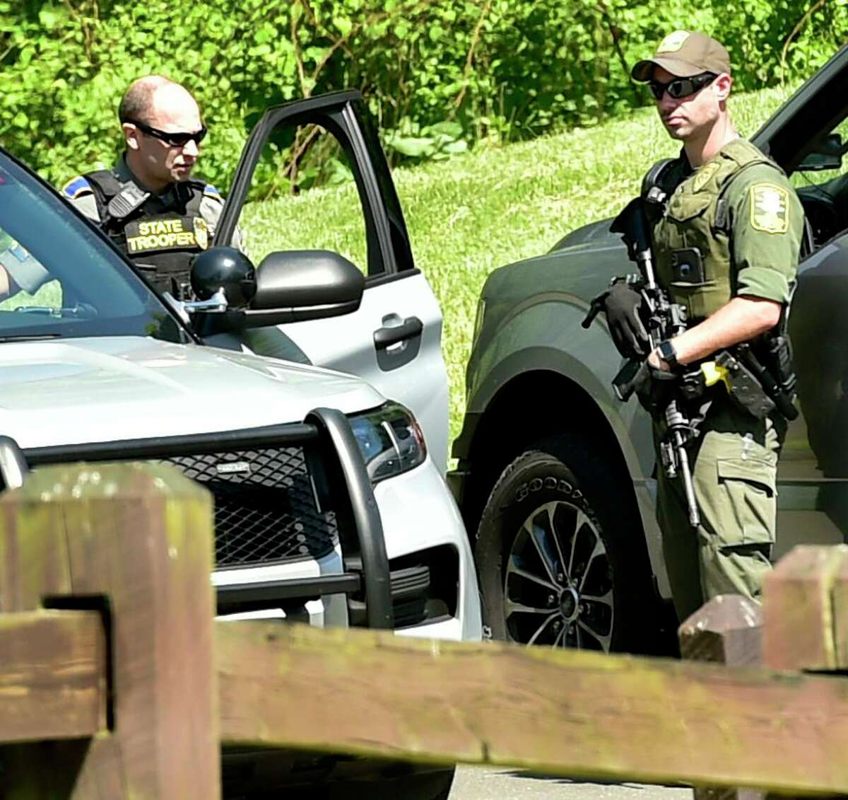 Derby, Connecticut - Sunday, May 24, 2020: Connecticut D.E.E.P Police officer, right, talks with a State Trooper during the search for suspected murderer Peter Manfredonia, 23, described as armed and dangerous Sunday morning at Osbornedale State Park in Derby after a stolen vehicle linked to the suspect was found on Hawthorne Avenue near Cullens Hill Road in Derby. The area borders Osbornedale State Park.The discovery launched an extensive search of the park and on local streets and in neighborhoods near Osbornedale and Roosevelt Drive where law enforcement secured another crime scene thought to be connected to Manfredonia. State Police said Manfredonia is believed to be armed with pistol and long guns. Manfredonia is wanted in a homicide and serious assault in northeastern Connecticut.