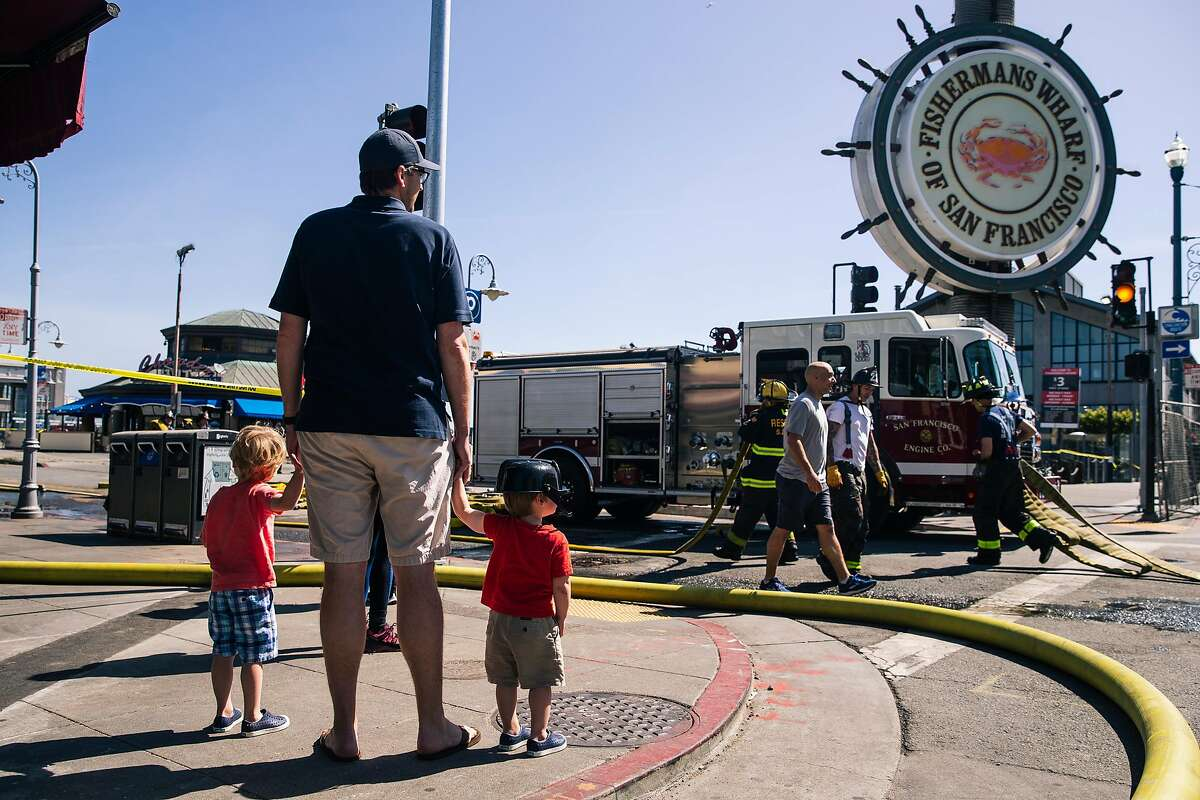 A family with a child wearing a toy firefighter hat, names declined, watch members of the San Francisco Fire Department work at the scene of a four alarm structure fire at Pier 45 in San Francisco, Calif. on Saturday, May 23, 2020.