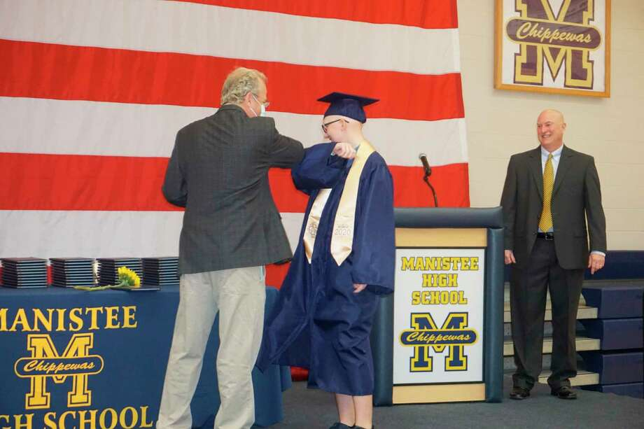 Manistee Area Public Schools Board of Education president Dr. Paul Antal and Trista Arnold do an elbow bump gesture during graduation proceedings while Manistee High School Principal Andrew Huber (right) smiles on Saturday. (Courtesy photo)