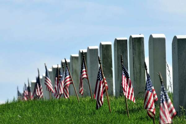 Endless row of white marble gravestones continues above hilltop at the Arlington National Cemetery in Arlington, Virginia, near Washington DC. U.S. flags decorating each grave to mark the Memorial Day. Narrow DOF at the flag right of center.
