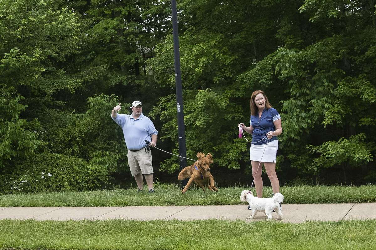 A supporter gives a thumbs up as the motorcade for President Donald Trump passes by en route to Trump National Golf Club, Sunday, May 24, 2020, in Sterling, Va. (AP Photo/Alex Brandon)