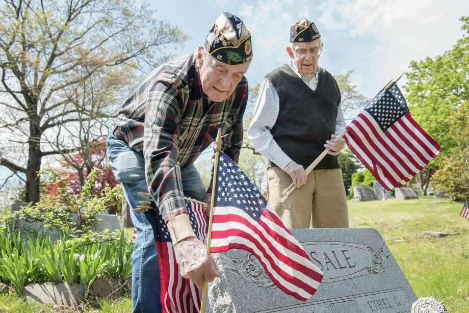 American Legion members Bing Ventres, left, and Judd Mott place flags at the graves of Wilton veterans at Hillside Cemetery in honor of Memorial Day 2020. Photo: Bryan Haeffele / Hearst Connecticut Media / BryanHaeffele
