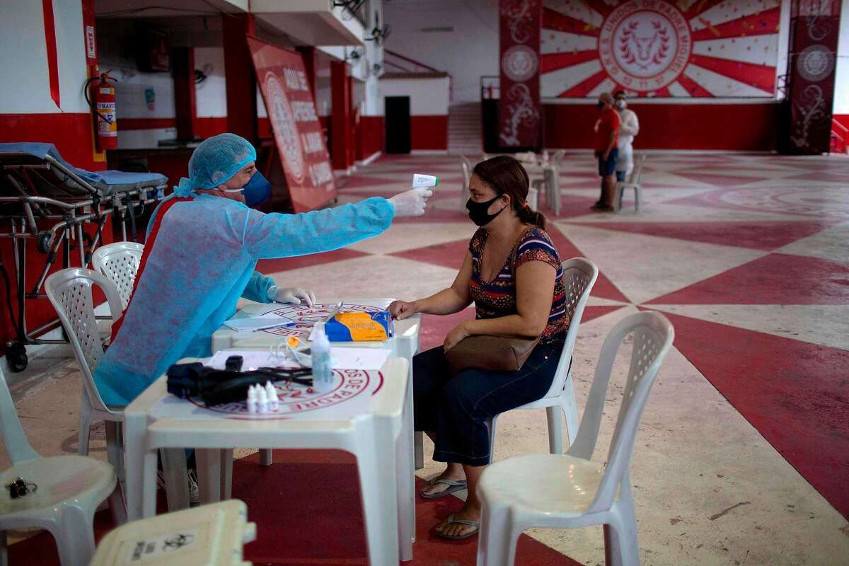 A physician checks the temperature of a woman with symptoms of the new COVID-19 coronavirus at the Unidos de Padre Miguel samba school headquarters in Rio de Janeiro, Brazil, on May 24, 2020.