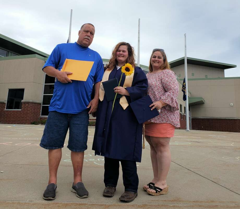 Gabrielle Guenthardt (center) is shown with diploma and class flower in hand next to father Wayne Guenthardt (left) and mother Pam Sievert (right) on Saturday.