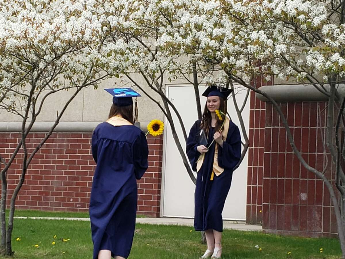 Jessica and Julia Gutowski take photos with their sunflowers and diplomas under flowering trees at Manistee High School Saturday.