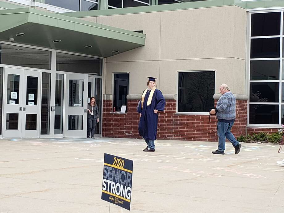 Graduating seniors and family members could be seen taking photos before entering  Manistee High School for commencement on May 23. Photo: Arielle Breen/News Advocate
