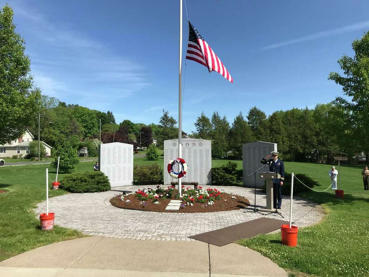 Retried Coast Guard Lt. Cmdr. Timothy Dickerson, USCG emcee for the ceremony, salutes as the colors are presented at the Portland Veterans Memorial on Sunday.