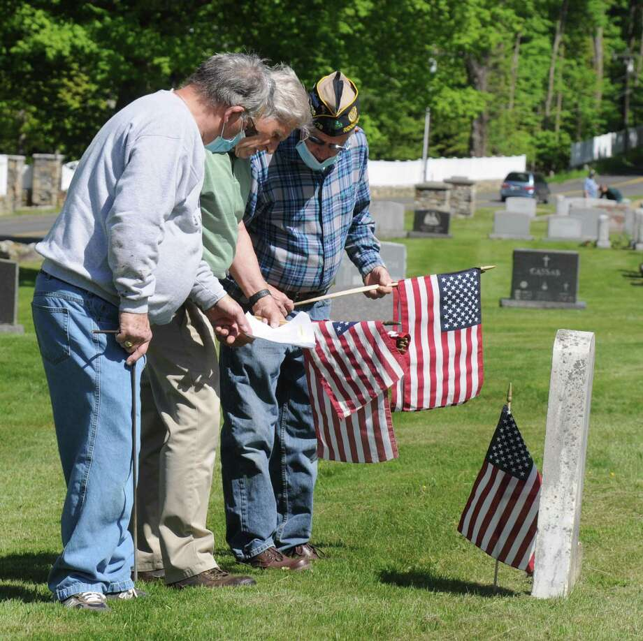 Mike Liberta, George Schuster and John Knoche look for the name of the veteran whose grave they'll honor with a small American Flag. Photo: Macklin Reid / Hearst Connecticut Media