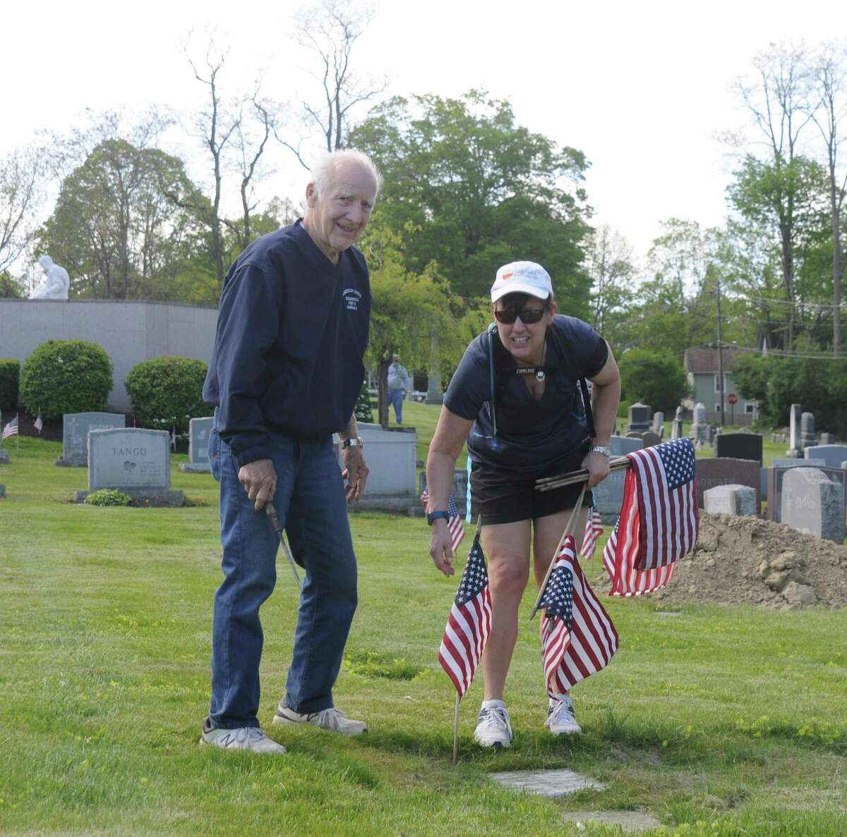 The father-daughter team of Bob and Kathy Tulipani worked in St. Mary's Cemetery, setting out flags to honor veterans graves.