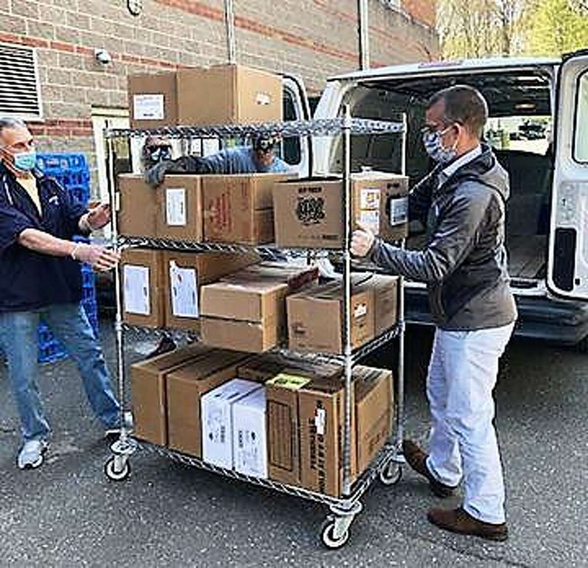 Bob Lisi, Ansonia schools youth outreach officer, left, and TEAM President/CEO David Morgan, right, load frozen food for donation.