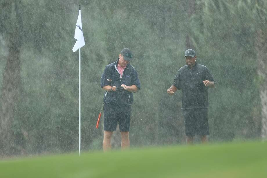 Former NFL quarterback Peyton Manning and Tiger Woods endure the rain on the 13th green at Medalist Golf Club. They teamed to beat Tom Brady and Phil Mickelson 1-up. Photo: Mike Ehrmann / Getty Images For The Match