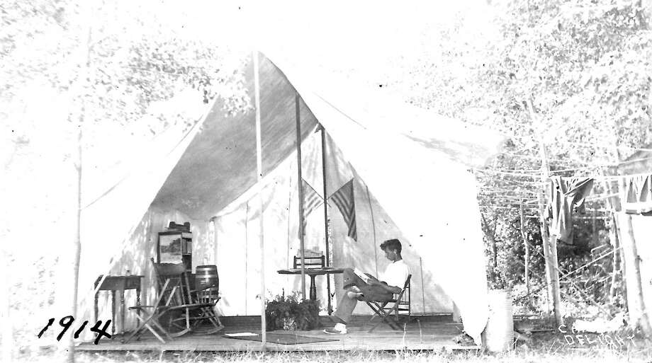 A camper relaxes in his tent house at Camp Delight during the summer of 1914.