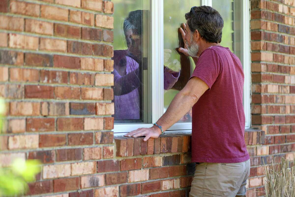 Jack Campise talks with his mother, Beverly Kearns, through her apartment window at the Kimberly Hall North nursing home, Thursday, May 14, 2020 in Windsor, Conn. The coronavirus has had no regard for health care quality or ratings as it has swept through nursing homes around the world, killing efficiently even in highly rated care centers. Preliminary research indicates the numbers of nursing home residents testing positive for the coronavirus and dying from COVID-19 are linked to location and population density a€?