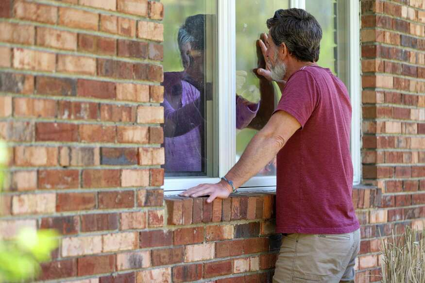 """Jack Campise talks with his mother, Beverly Kearns, through her apartment window at the Kimberly Hall North nursing home, Thursday, May 14, 2020 in Windsor, Conn. The coronavirus has had no regard for health care quality or ratings as it has swept through nursing homes around the world, killing efficiently even in highly rated care centers. Preliminary research indicates the numbers of nursing home residents testing positive for the coronavirus and dying from COVID-19 are linked to location and population density a€?"""" not care quality ratings. (AP Photo/Chris Ehrmann"""