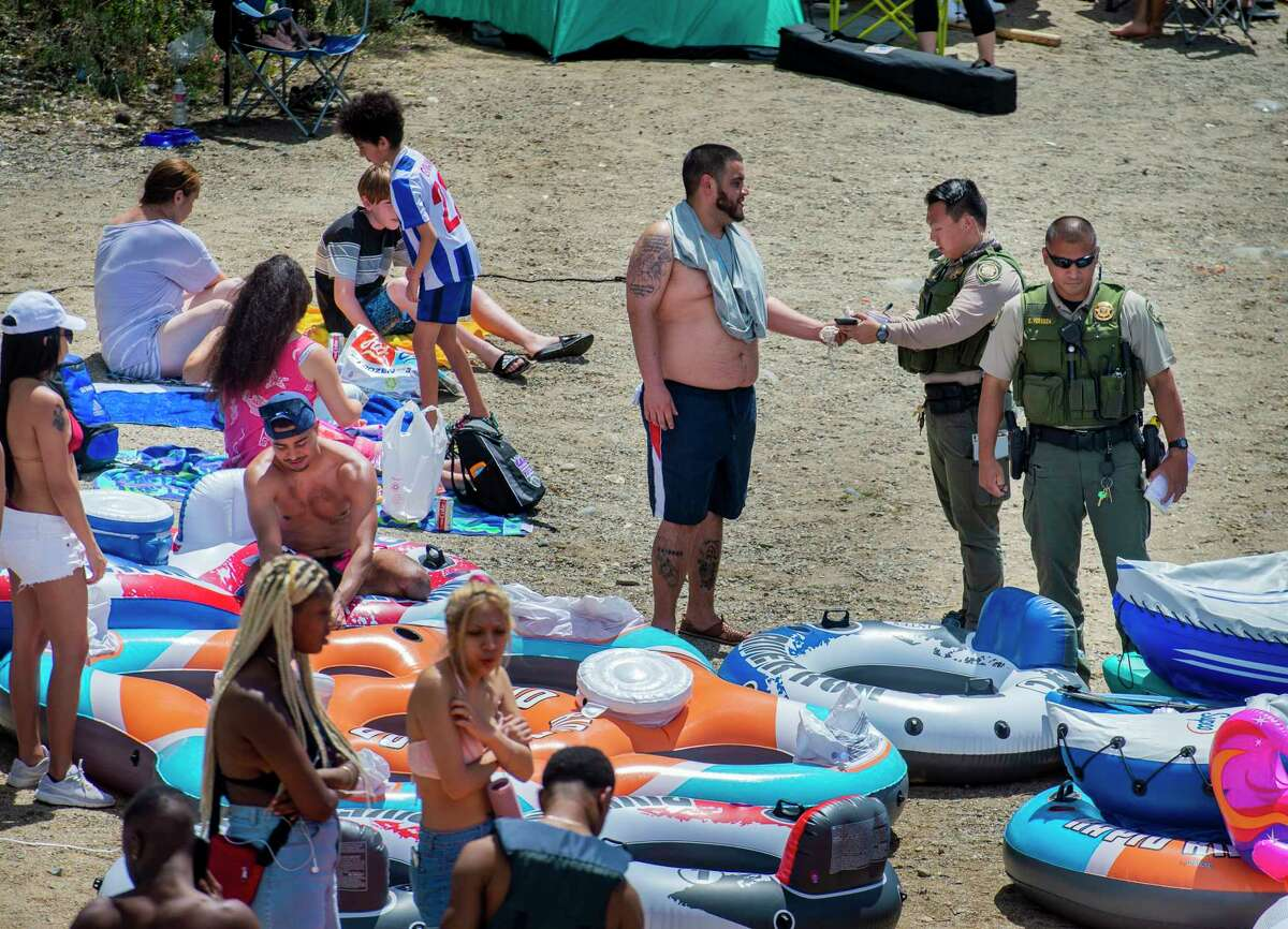 A Sacramento County park ranger issues an alcohol citation to an American River visitor in the Sunrise Recreation Area near Rancho Cordova, Calif., during the Memorial Day weekend, Sunday, May 24, 2020. Alcohol is banned along the shoreline of the river between Hazel and Watt avenues on Memorial Day weekend, the Fourth of July and Labor Day weekend. (Daniel Kim/The Sacramento Bee via AP)