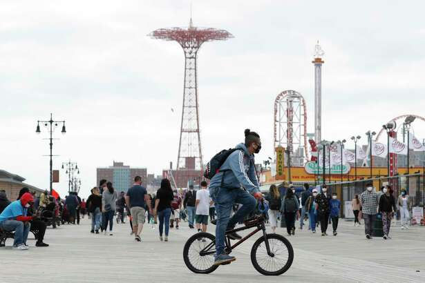 A young man wearing a protective face mask rides his bicycle along a fairly crowded Coney Island boardwalk during the current coronavirus outbreak, the afternoon of Sunday, May 24, 2020, in New York. No swimming was allowed and social distancing reminders were abundant on the beach as Memorial Day weekend kicked off the first weekend of summer.