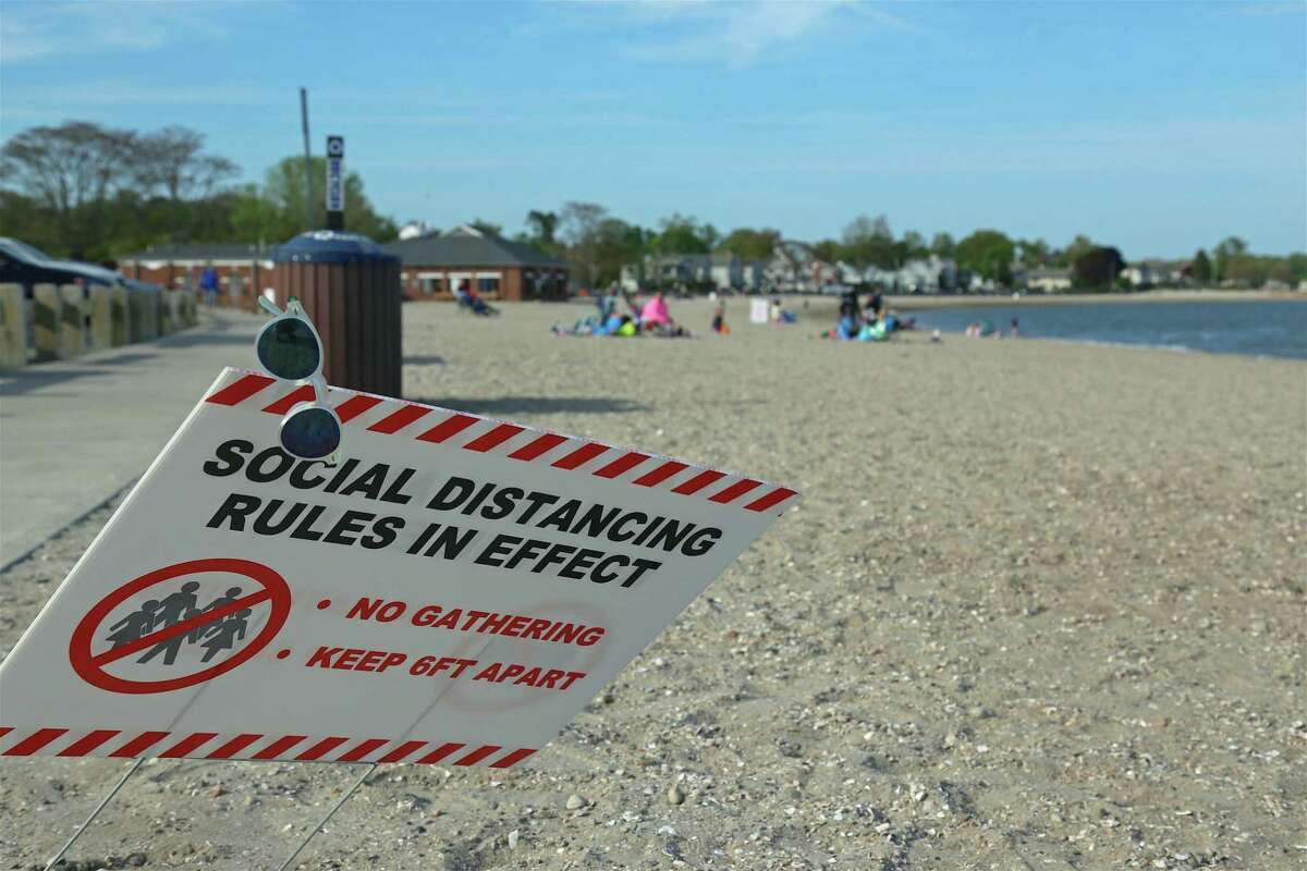 One of several signs stretching along the sand at Compo Beach on Sunday, May 24, 2020, in Westport, Conn.