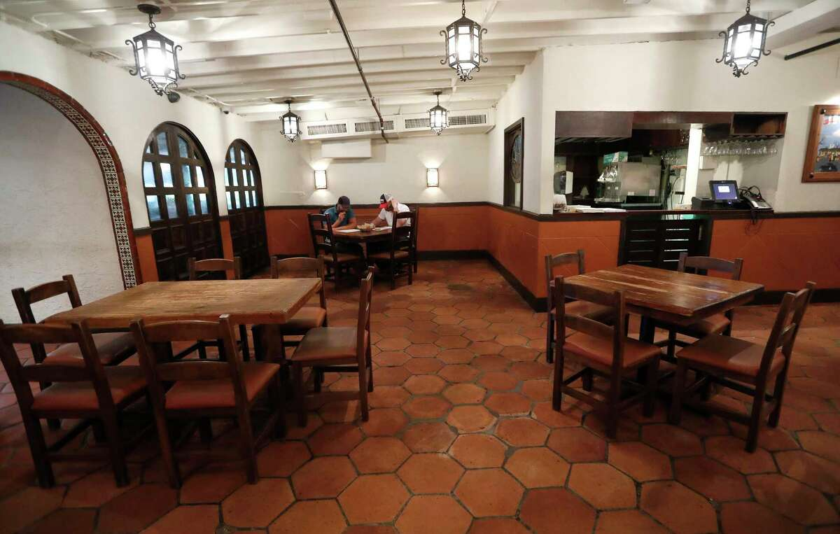 Two men sit at a table with two empty tables spaced properly apart in the dining room at the Original Ninfa's on Navigation Drive, in Houston, Friday, May 1, 2020, as the Houston restaurant community takes a big step Friday as restaurants were allowed to reopen at 25 percent capacity.
