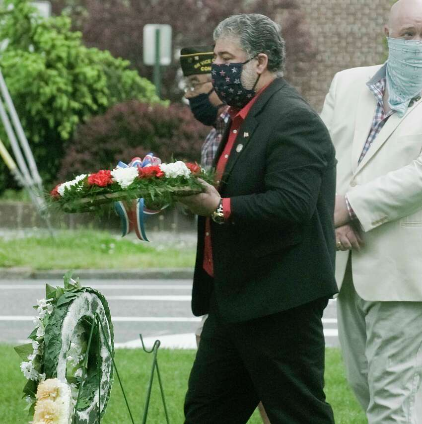 Mayor Pete Bass carries a wreath for a dedication at Veterans Bridge during New Milford's Memorial Day Service. Monday, May 25, 2020