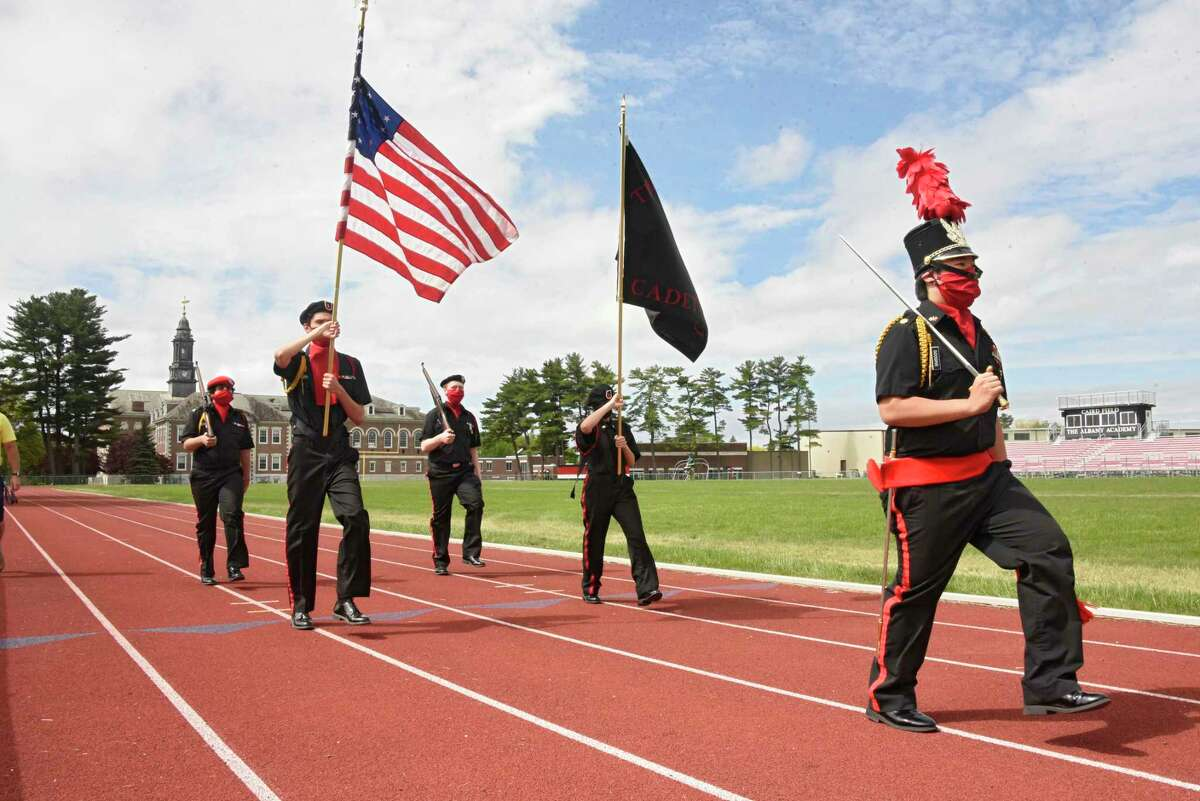 Albany Academy Cadet Corps, from left, Zain Jafri, Silas Strich, Erik Payton, Callie Koenig and Major Jack Googins march on the school?•s track to honor those who have died in military service to their country and to New Yorkers who have died from COVID-19 on Monday, May 25, 2020 in Albany, N.Y. The cadets, who usually march in the City of Albany?•s Memorial Day parade came up with the idea to honor the military and also march a step for every person in New York who has died from the coronavirus. The cadets marched 9 laps for 2.25 miles. (Lori Van Buren/Times Union)