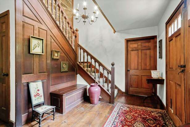 The foyer features a custom staircase, wood paneled and a stone wall, and a wide-planked hardwood floor.