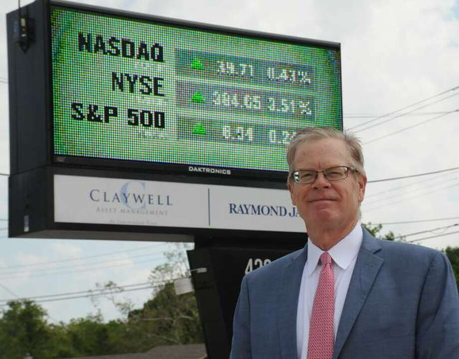 James Claywell of Claywell Asset Management stands outside his firm's market sign at 3014 Godfrey Road in Godfrey. During volatile markers, he and other area investment advisers say the key is to formulate a good investment plan and stick with it.