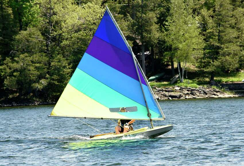 A man is seen on a small sailboat near the beach at Thompson's Lake Campground on Monday, May 25, 2020 in East Berne, N.Y. Most campsites at the campground were empty due to a mandate of no camping at state campgrounds due to COVID-19. Although, some people were day picnicking on the campsites. (Lori Van Buren/Times Union)