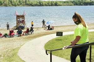Staff wearing masks were making sure people practiced social distancing and disinfected handrails at the beach at Thompson's Lake Campground on Monday, May 25, 2020 in East Berne, N.Y. Most campsites at the campground were empty due to a mandate of no camping at state campgrounds due to COVID-19. Although, some people were day picnicking on the campsites. (Lori Van Buren/Times Union)