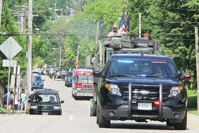 Vehicles head up College Avenue from the Alton Middle School parking lot during the 153rd annual Alton Memorial Day Parade. The parade, billed as one of the longest continuous Memorial Day parades in the country, had been cancelled because of the coronavirus pandemic, but some organizers set up a smaller parade with about a half-dozen vehicles. However, others showed up and eventually almost 40 vehicles participated.