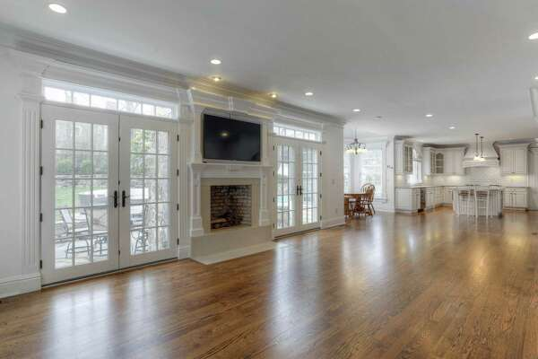 The family room features a fireplace and two sets of French doors topped with transoms to the patio and yard.