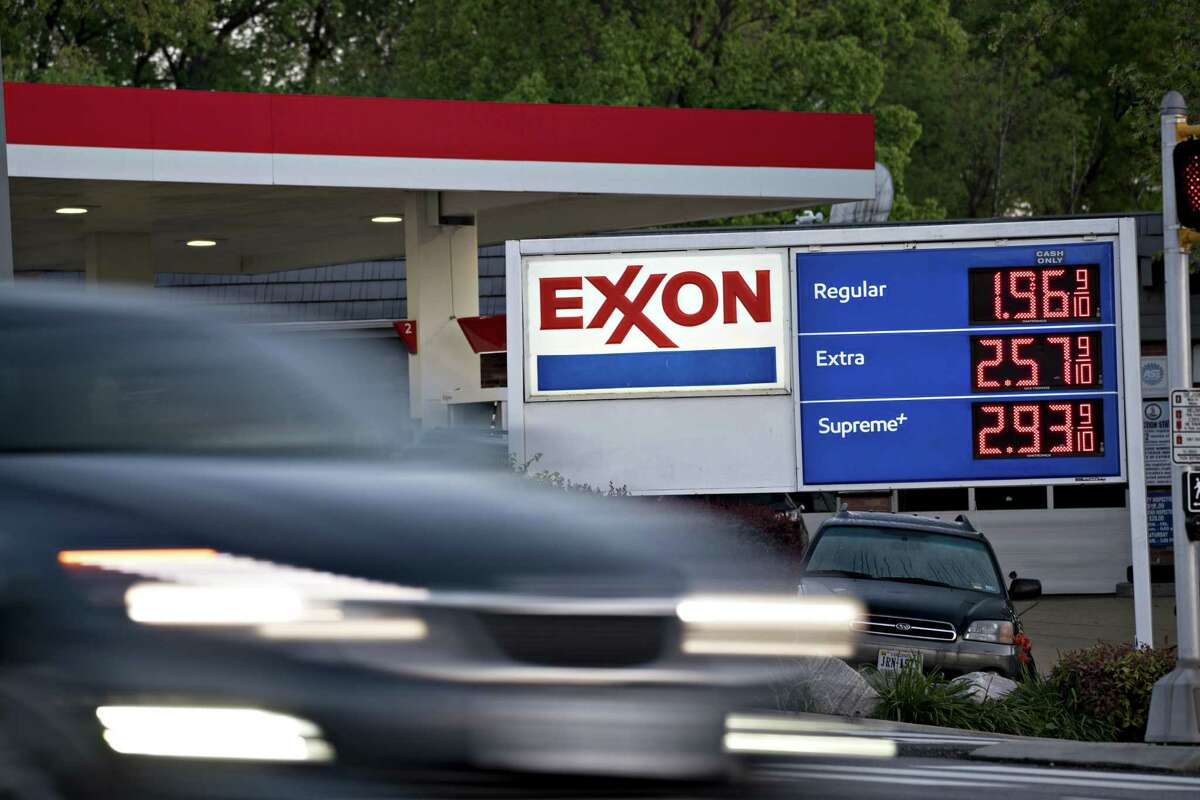 A vehicle passes an Exxon Mobil Corp. gas station. The plunge in petroleum demand has hit the energy industry, including oil majors. U.S. road fuel demand is forecast to fall by 1.1 million barrels per day to 10.1 million barrels per day, down from last year's 11.2 million barrels per day, according to Rystad Energy, a Norwegian research firm.