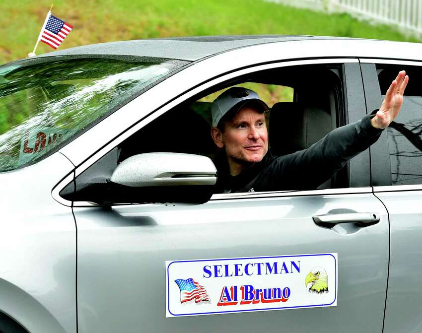 Seymour, Connecticut - Monday, May 25, 2020: A man waves during Memorial Day drive-by procession of vehicles parade by the Emma Street home in Seymour Monday of World War II U.S. Navy veteran John Maiorino.