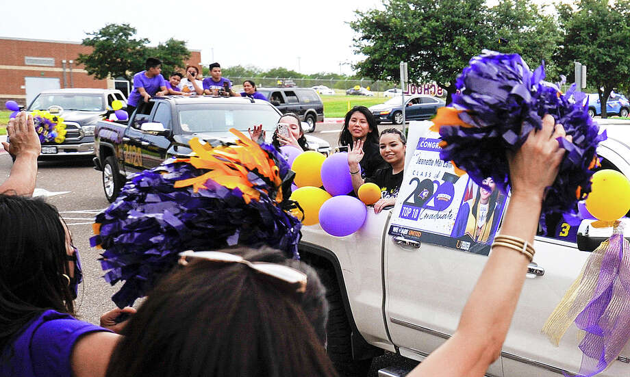 Lyndon B. Johnson High School graduating seniors, driven by friends and family, ride past the front of the school as faculty members cheer them on, Saturday, May 23, 2020, as the students participate in a parade in lieu of their prom. Photo: Danny Zaragoza/Laredo Morning Times