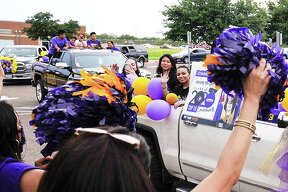 Lyndon B. Johnson High School graduating seniors, driven by friends and family, ride past the front of the school as faculty members cheer them on, Saturday, May 23, 2020, as the students participate in a parade in lieu of their prom.